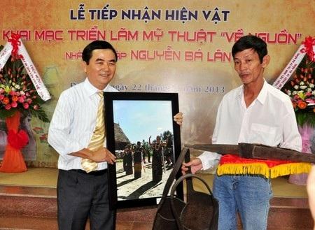 Ông Lâm Tứ Khoa (phải) trao tặng cung tên, gùi của đồng bào các dân tộcCơtu ở Quảng Nam