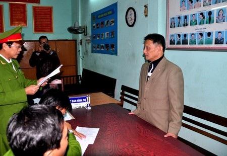 Ông Bùi Mạnh Hùng (phải) nghe lệnh bắt tạm giam