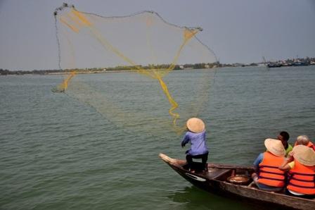 Du khách đang chăm chú theo dõi cách quăng chài của ngư dân