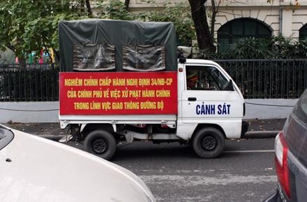 Một chiếc xe của công an phường đi tuần trên phố Lê Lai, bên hông vườn hoa Lý Thái Tổ