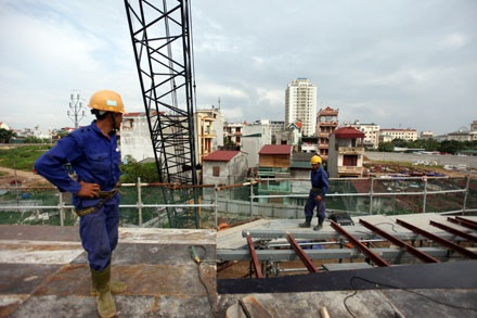 Công nhân thi công trên đường dẫn, ngay bên cạnh là cả trăm hộ dân vẫn đang sinh sống