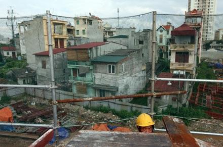 Hàng rào tôn ngăn tạm phân cách công trường và các hộ dân chưa giải tỏa