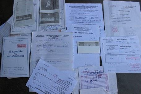 Chồng giấy tờ, bệnh án, phiếu khám liệt kê bệnh tật của anh Khôi và cháu Ny