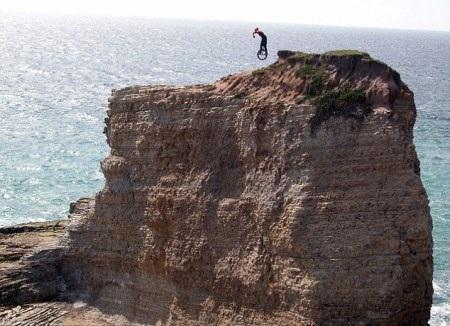 Kris Holm và chiếc xe một bánh của mình trên một núi đá ở bãi biển