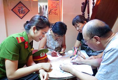 CSKV Công an TP Hà Nội hướng dẫn người dân làm thủ tục sang tên, di chuyển xe. (Ảnh: Nguyễn Hưng)