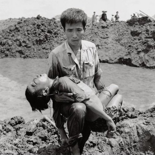 Người đàn ông bế xác của một cậu bé sau vụ ném bom của Mỹ xuống Hải Phòng tháng 8/1972.
