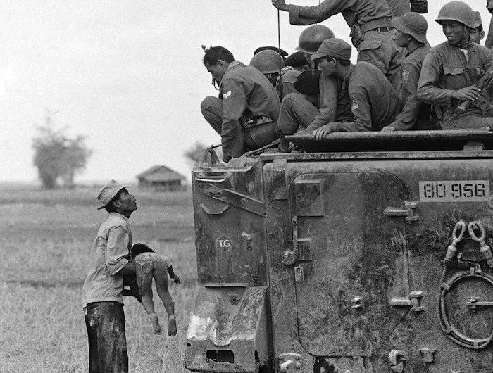 Một người đàn ông đang bế đứa con đã chết gần biên giới Campuchia ngày 19/3/1964.