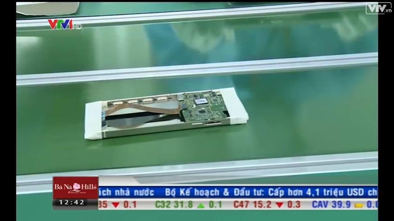 Một công nhân đang thao tác lấy viên pin để ráp vào máy. Viên pin còn nguyên băng dính.