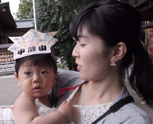 Một bé trai mắt ngấn nước trong vòng tay mẹ