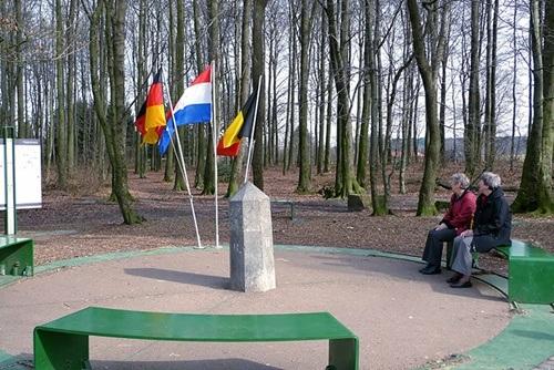 Đường biên giới đơn sơ có cắm cờ của cả 3 quốc gia Đức, Hà Lan và Bỉ.