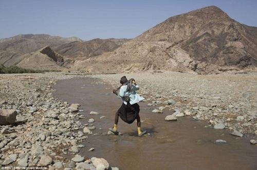 Một người dân đi trên mặt nước hồ sắp cạn khô nước
