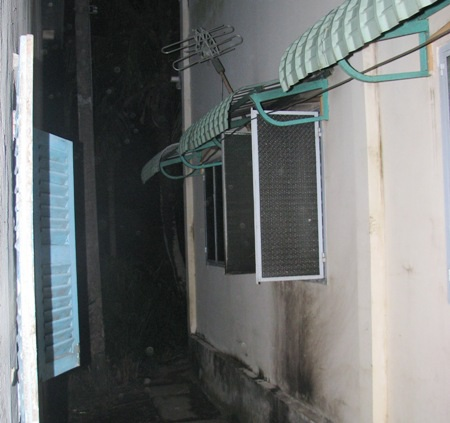 Cửa sổ bên hông nhà nơi hung thủ tưới xăng và quăng mồi lửa vào bên trong...