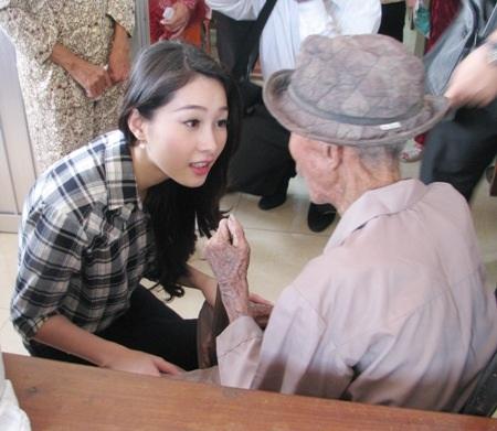 Hoa hậu thăm hỏi một cụ già ở Cần Thơ trong một chuyến đi trao quà từ thiện năm 2012.