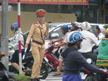 Một nữ CSGT thổi còi liên tục để hướng dẫn xe đi.