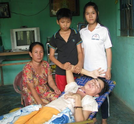 Hai chị em Khánh Ngân, Khánh Dương bên bà ngoại và người cha nằm liệt giường.