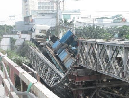 Một bên cầu tạm cầu Vồng gãy gập hẳn xuống lòng sông dưới sức nặng của xe tải có tải trọng 60 tấn.