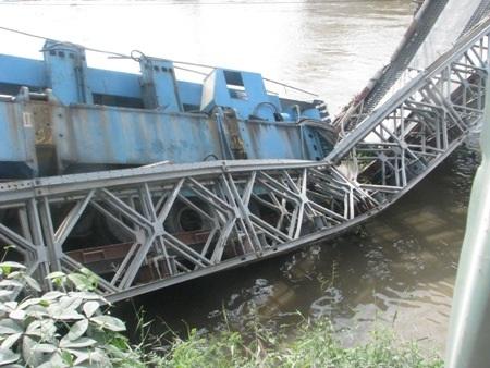 ...trong khi phần thân xe nằm gọn trong lòng cầu tạm phía dưới sông.