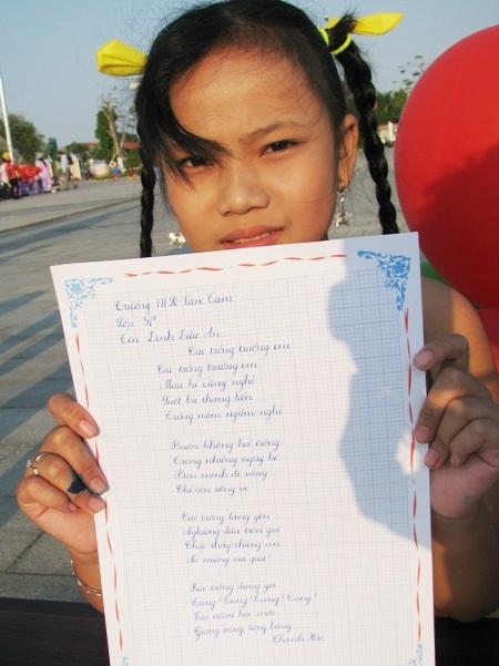 Một em học sinh khoe tác phẩm của mình.