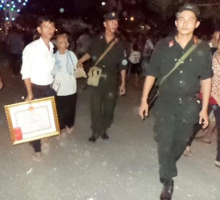 Hình ảnh 2 chiến sĩ cảnh sát Sóc Trăng giúp mẹ Việt Nam anh hùng tại buổi lễ.
