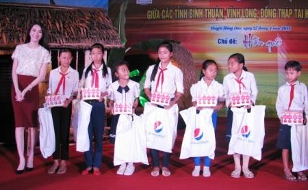 Hoa hậu Việt Nam 2012 Đặng Thu Thảo trao quà đến các học sinh nghèo.