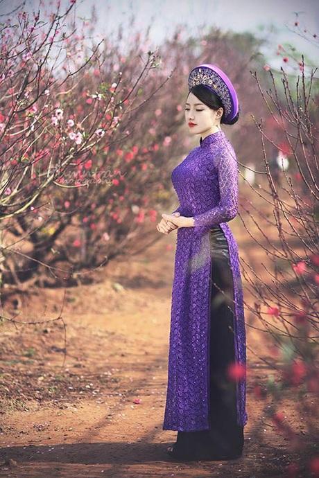 Cô khoác lên mình chiếc áo dài tím nổi bật giữa vườn đào hồng thắm