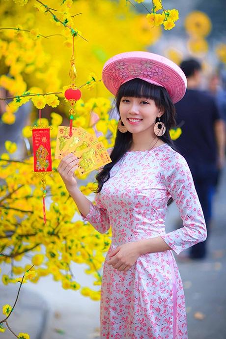 Út Phương nổi bật trên phố với tà áo dài họa tiết hoa đào.
