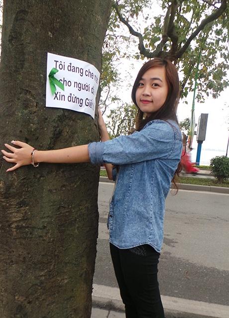 Thành viên nhóm tình nguyện ôm cây thể hiện tình yêu với một Hà Nội xanh