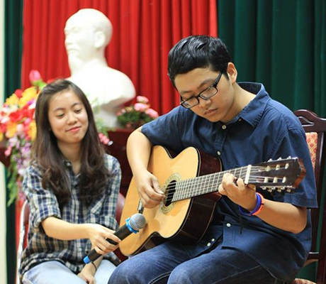 Quốc Chinh chơi đàn guitar trong một chương trình văn nghệ sinh viên