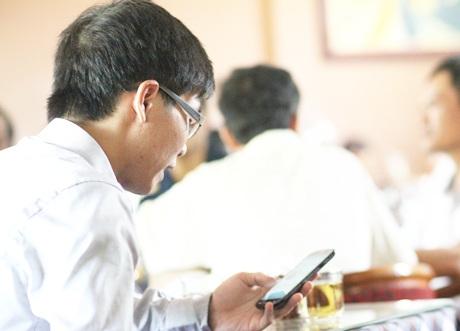 Phụ huynh tranh thủ làm việc, đọc báo qua điện thoại trong lúc chờ con thi