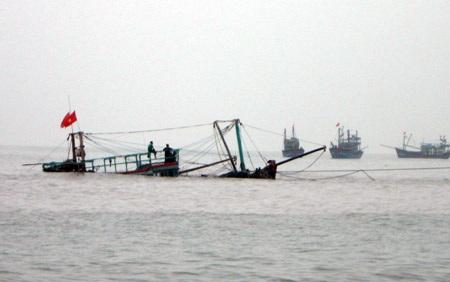 Tàu cá mang số hiệu NA 93223 TS bị va phải đá ngầm chìm xuống biển, may mắn 10 ngư dân thoát nạn.