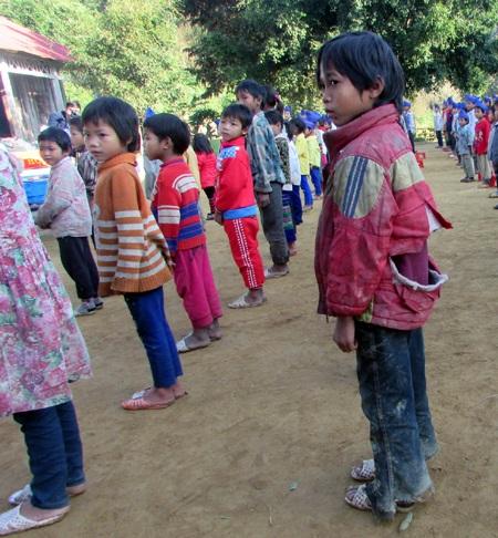 Một học sinh quần áo lấm lem bùn, áo rách tướp.