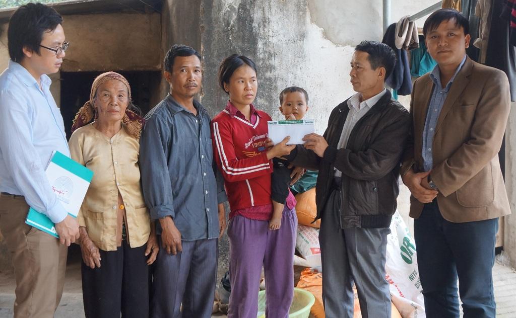 Ông Hồ Văn Ninh - PCT UBND xã Nghi Kiều trao quà đến chị Hóa.
