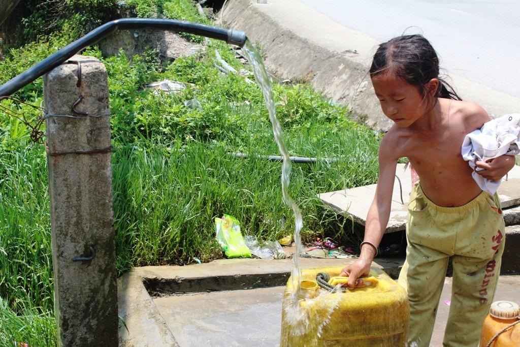 """Em bé người dân tộc tranh thủ lúc đi lấy nước để tắm """"giải nhiệt""""."""