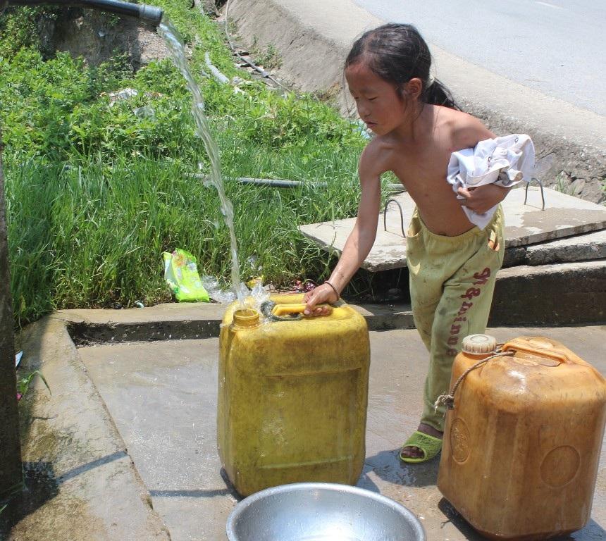 Những em bé phải thay bố mẹ đi xa lấy nước về để dùng.