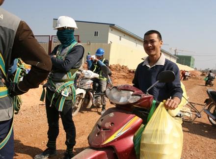 Một chủ cửa hàng cơm mang cơm hộp vào tận cổng nhà máy để phục vụ công nhân.