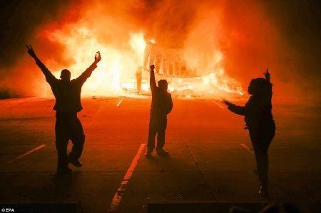 3 người biểu tình hò reo trước một cửa hàng bị phóng hỏa
