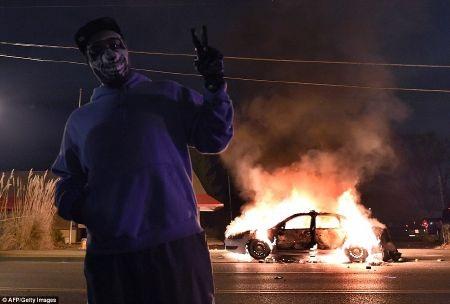 Một người biểu tình đeo mặt nạ chụp ảnh trước một xe cảnh sát bị phóng hỏa