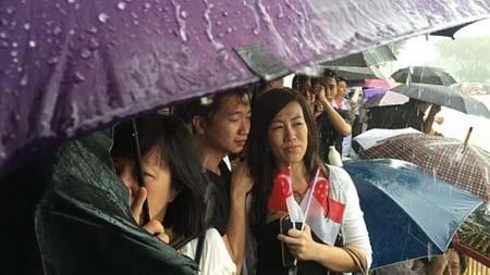 Người dân phải dùng ô để che mưa trong khi chờ đợi đoàn rước