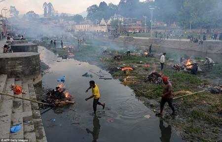 Các nạn nhân tử nạn được hỏa táng vội vã bên một con sông (Ảnh: AFP)