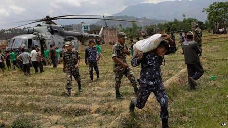 Một binh sỹ quân đội Nepal chuyển hàng cứu trợ ra khỏi một trực thăng của Ấn Độ (Ảnh: AP)