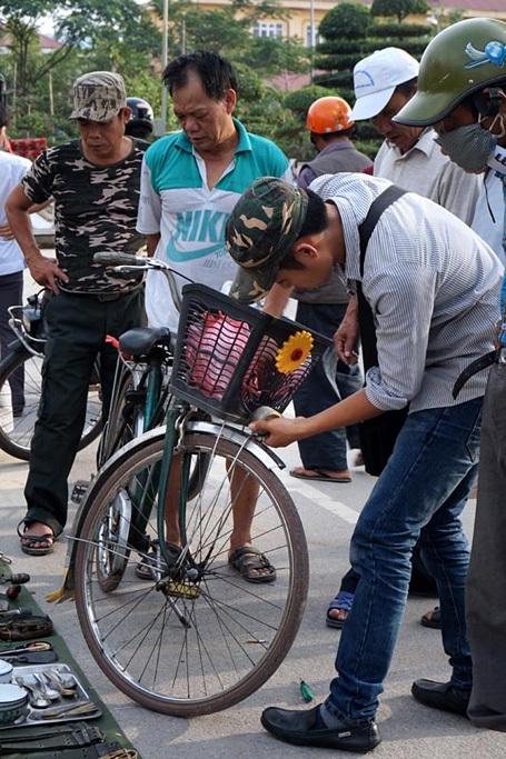 Một người đàn ông tháo chiếc đèn trên xe peugeot của mình bán giữa chợ.
