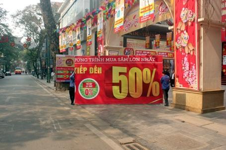 Một cửa hàng điện máy trên phố Tràng Thi đang chuẩn bị những tấm biển giảm giá dịp cuối năm