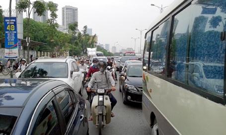 Người điều khiển xe máy tìm cách luồn lách qua ô tô để thoát khỏi cảnh ùn tắc
