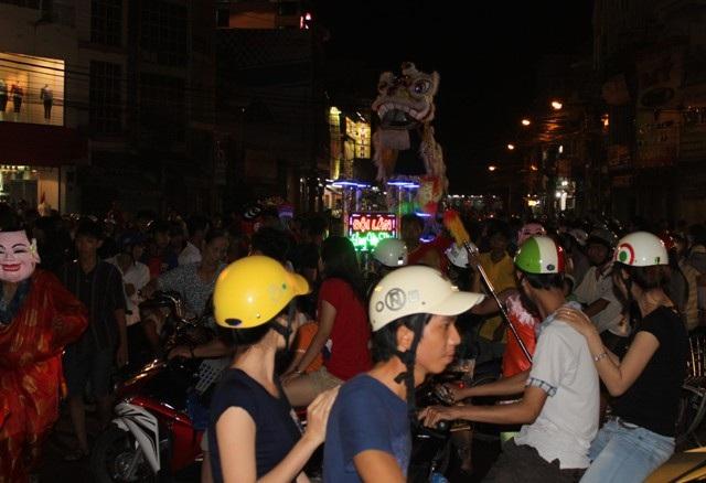 Đường phố chật kín người đi xem múa lân.