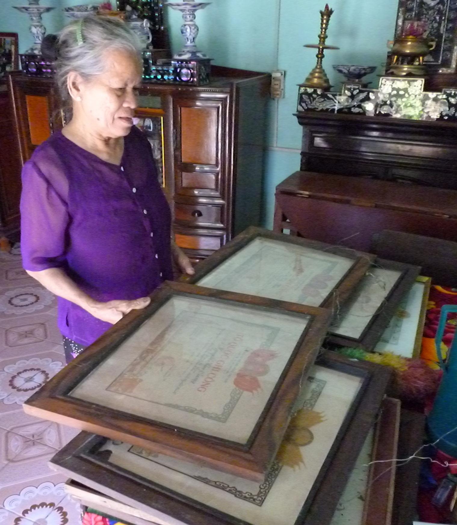 Bà Đào lấy những tấm Huân chương kháng chiến của chồng và con đã hy sinh cho Tổ quốc.