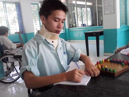 Nguyễn Thanh Huy ngồi xe lăn tập cử động bàn tay (Ảnh: Chí Thanh)