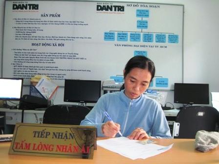 Chị Kiều làm thủ tục nhận 128.090.000 đồng do bạn đọc Dân trí ủng hộ