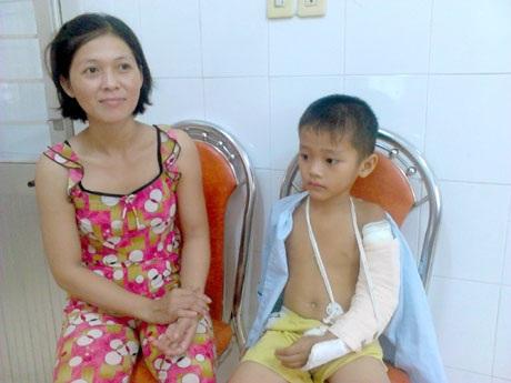 Cháu L.T.P. với cánh tay băng bó sau tai nạn ở lò gạch