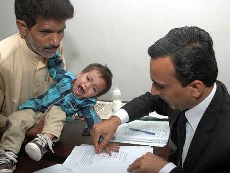 Bé Mosa Khan khóc khi nhân viên tòa án lấy dấu vân tay của bé để lưu lại hồ sơ