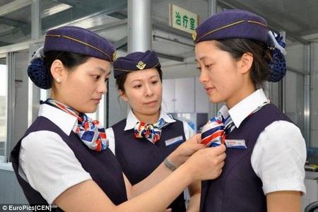 Các y tá đang chỉnh sửa trang phục cho nhau